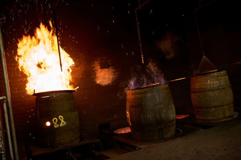 Several whiskey barrels getting charred by a large flame